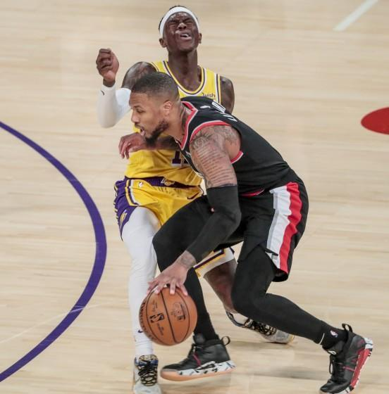 Lakers guard Dennis Schroder fouls Trail Blazers guard Damian Lillard as he drives during a game at Staples Center.