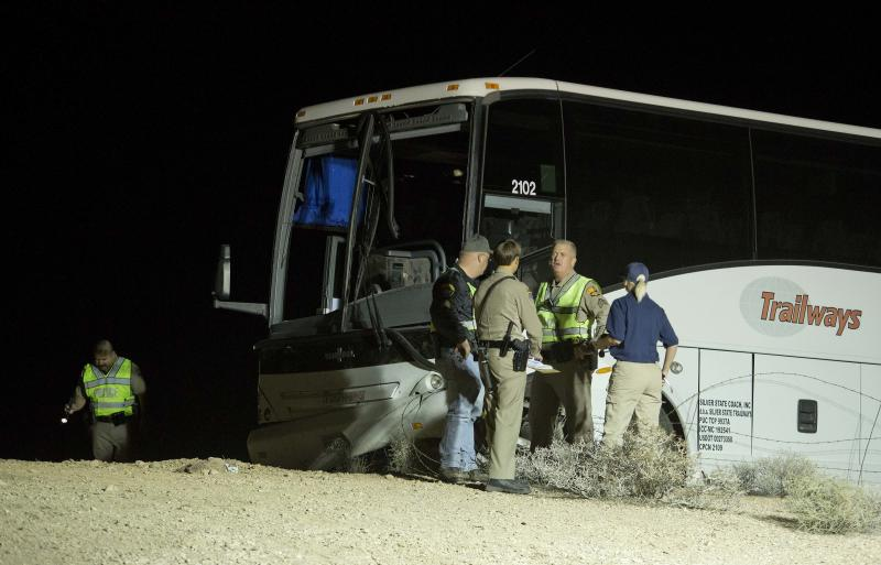 Arizona Highway Patrol officers examine the exterior of a tour bus that careened off the highway and crashed off northbound Highway 93, Friday, Oct. 19, 2012, near Willow Beach, Ariz. The crash killed the driver and left at least four passengers with serious injuries. About 45 other passengers were less seriously hurt and not all of them required hospital treatment, the Arizona Highway Patrol said. (AP Photo/Julie Jacobson)