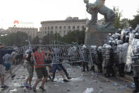 Protesters throw barricades at riot police in Belgrade, Serbia, Wednesday, July 8, 2020. Police have fired tear gas at protesters in Serbia's capital during the second day of demonstrations against the president's handling of the country's coronavirus outbreak. President Aleksandar Vucic backtracked on his plans to reinstate a coronavirus lockdown in Belgrade this week, but it didn't stop people from firing flares and throwing stones while trying to storm the downtown parliament building. (AP Photo/Marko Drobnjakovic)