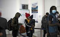 Haitians with Chilean residency permits at Arica airport in Chile, waiting to catch a flight to Santiago after crossing the border from Peru (AFP/MARTIN BERNETTI)
