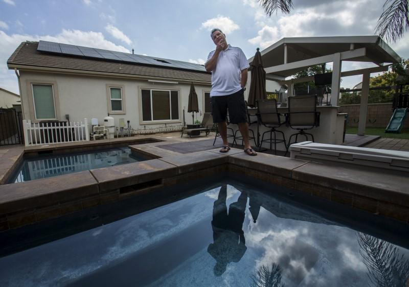 Home owner Steven Lista stands in his back yard under the solar panels he financed using a government sponsored system in Eastvale, California