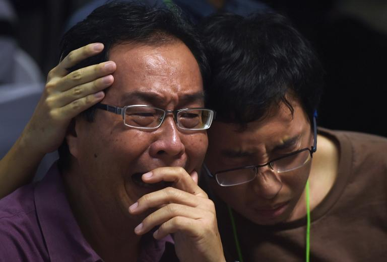 Family members of passengers onboard AirAsia flight QZ8501 react after watching news reports showing a body floating in the Java Sea, while waiting at a crisis-centre set up at Juanda International Airport in Surabaya, on December 30, 2014