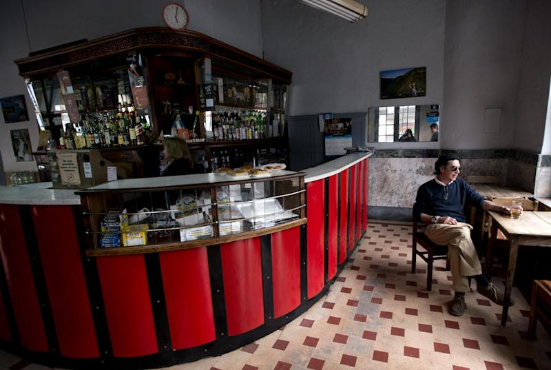 In this Aug. 21, 2013 photo, a man sits with a drink in hand at a downtown bar in Montevideo, Uruguay. The government of Uruguay makes Scotch whisky. It also makes and sells rum, vodka and cognac, and has done so for nearly a century. President Jose Mujica says Uruguay's long experience at the center of the nation's liquor business makes it more than capable of dominating another addictive substance: marijuana. (AP Photo/Matilde Campodonico)