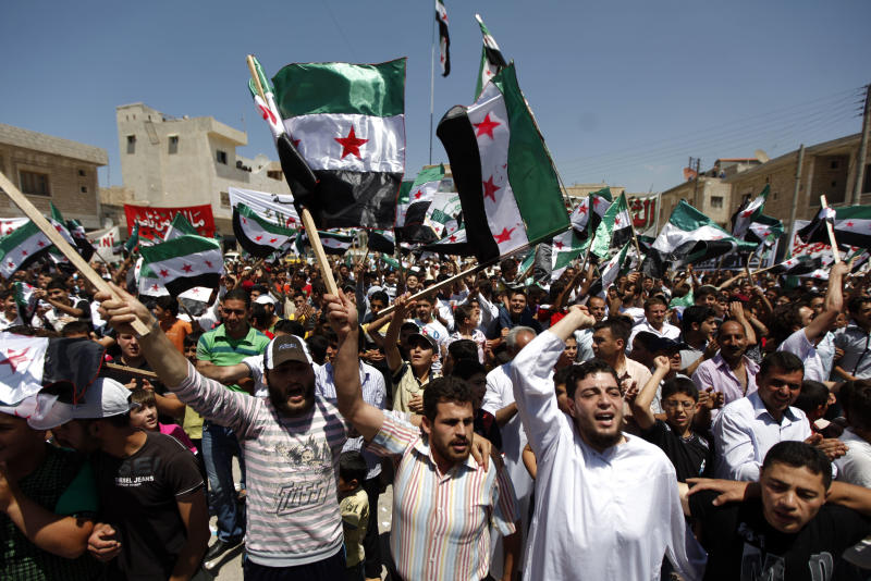 Syrians attend an anti-Bashar Assad protest after Friday prayers on the outskirts of Idlib, Syria, Friday, June 8, 2012. (AP Photo)
