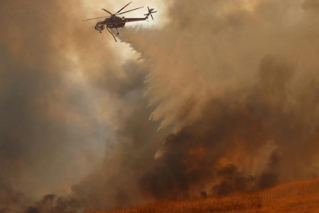 <p>A helicopter drops water on a wind driven wildfire in Orange, Calif., Oct. 9, 2017. (Photo: Mike Blake/Reuters) </p>