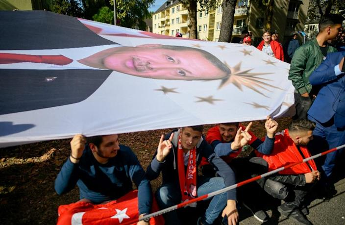 As well as protesters, wellwishers took to the streets of Cologne holding a huge portait of the Turkish president as he arrived to open one of Europe's largest mosques (AFP Photo/SASCHA SCHUERMANN)