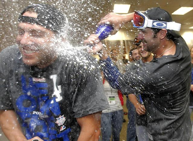 Los Angeles Dodgers' Scott Van Slyke, right, sprays a teammate after the Dodgers clinched the NL West title with a 7-6 win over the Arizona Diamondbacks in a baseball game Thursday, Sept. 19, 2013, in Phoenix. (AP Photo/Ross D. Franklin)