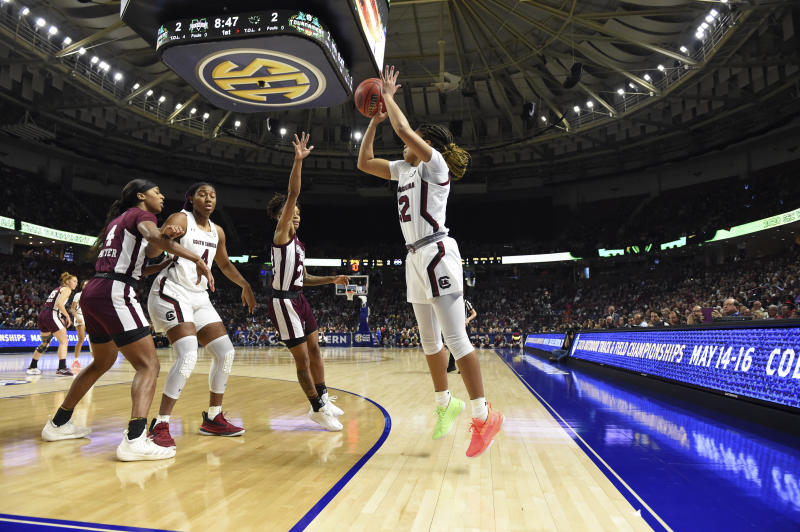 South Carolina's Tyasha Harris, right, shoots a three-point basketwhile defended by Mississippi State's Jordan Danberry, center right, during a championship match at the Southeastern Conference women's NCAA college basketball tournament in Greenville, S.C., Sunday, March 8, 2020. (AP Photo/Richard Shiro)