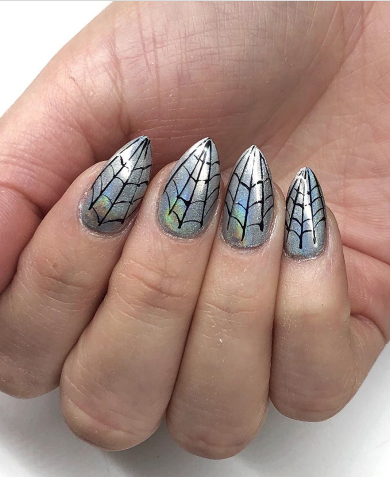 """<p>Go chrome or go home! Take inspiration from nail artist <a href=""""https://www.instagram.com/p/B-288u5D7wu/"""" rel=""""nofollow noopener"""" target=""""_blank"""" data-ylk=""""slk:Lauren VonLipstick"""" class=""""link rapid-noclick-resp"""">Lauren VonLipstick</a> who painted black spiderwebs on top of chrome nail polish for superhero vibes. </p><p><a class=""""link rapid-noclick-resp"""" href=""""https://www.amazon.com/Color-Club-Halographic-Polish-Multicolored/dp/B00ACTL94A?tag=syn-yahoo-20&ascsubtag=%5Bartid%7C10072.g.33239588%5Bsrc%7Cyahoo-us"""" rel=""""nofollow noopener"""" target=""""_blank"""" data-ylk=""""slk:SHOP HOLOGRAPHIC POLISH"""">SHOP HOLOGRAPHIC POLISH</a></p>"""