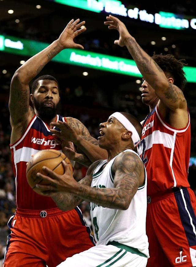 Isaiah Thomas of the Boston Celtics takes a shot against Markieff Morris (L) and Kelly Oubre Jr. of the Washington Wizards during the fourth quarter, at TD Garden in Boston, Massachusetts, on March 20, 2017 (AFP Photo/Maddie Meyer)