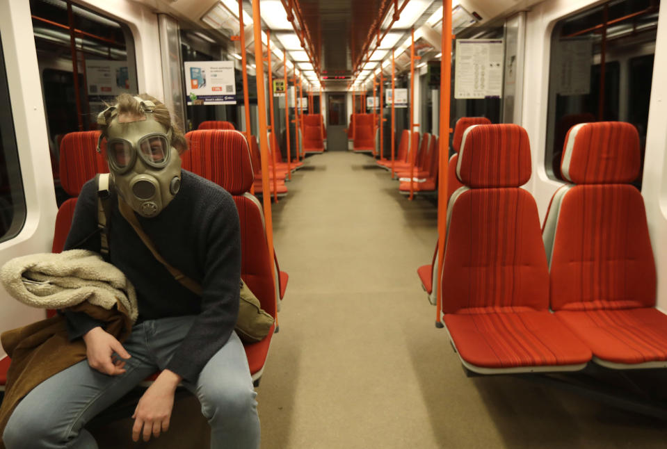 FILE - In this March 17, 2020 file photo a man wearing an old military gas mask rides the subway in Prague, Czech Republic. (AP Photo/Petr David Josek, File)