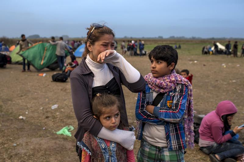 A migrant from Syria cries as she stands with her children on a field after crossing into Hungary from the border with Serbia near the village of Roszke, September 5, 2015. Austria and Germany threw open their borders to thousands of exhausted migrants on Saturday, bussed to the Hungarian border by a right-wing government that had tried to stop them but was overwhelmed by the sheer numbers reaching Europe's frontiers. Left to walk the last yards into Austria, rain-soaked migrants, many of them refugees from Syria's civil war, were whisked by train and shuttle bus to Vienna, where many said they were resolved to continue on to Germany. REUTERS/Marko Djurica