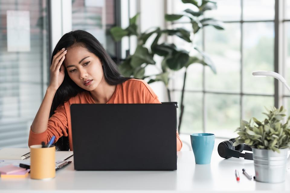 woman stressed about project in front of laptop while working from home.
