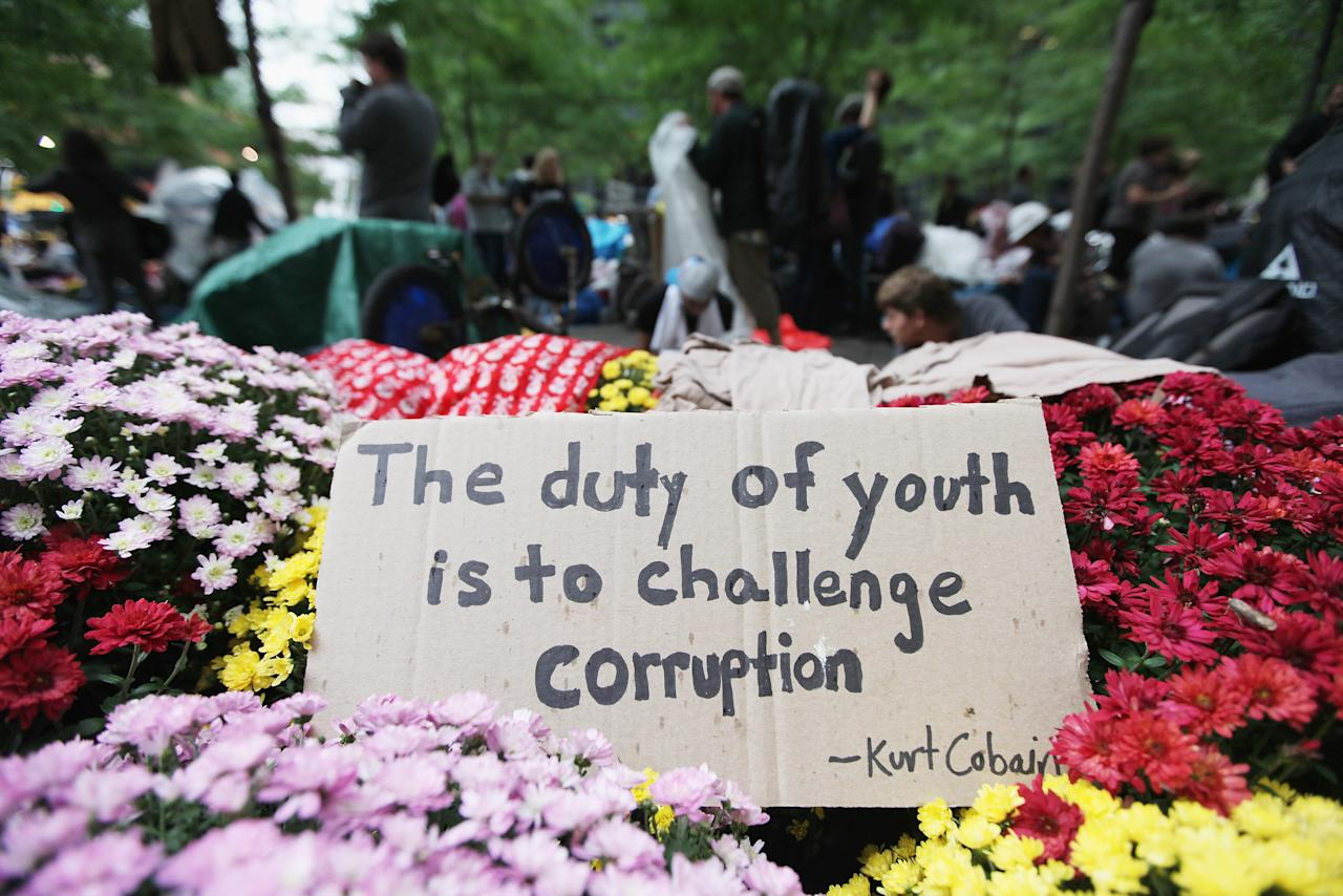 NEW YORK, NY - OCTOBER 01: A sign with a quote by Kurt Cobain written on it sits in Zuccotti Park along with members of the Occupy Wall Street movement before they marched to the Brooklyn Bridge on October 1, 2011 in New York City. The motorway portion of the bridge is not intended for pedestrians and as some of the marchers attempted to cross that portion, they were stopped midway by police. Hundreds of protesters were arrested.  (Photo by Mario Tama/Getty Images)