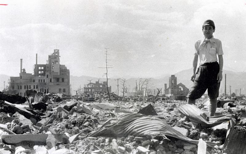 A man stand on the debris after the atomic bomb completely destroyed the city in August 1945 in Hiroshima - Getty Images Contributor