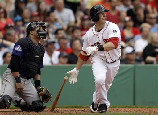 Boston Red Sox's Daniel Nava follows through on a sacrifice fly, driving in a run during the third inning of an interleague baseball game against the Colorado Rockies at Fenway Park in Boston, Wednesday, June 26, 2013. Rockies catcher Yorvit Torrealba watches at left. (AP Photo/Elise Amendola)