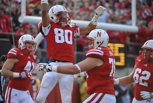 Nebraska's Kenny Bell (80) jumps into the arms of teammate Brent Qvale (76), after catching a touchdown pass against Minnesota in the first half of an NCAA college football game in Lincoln, Neb., Saturday, Nov. 17, 2012. At left is Jake Long (41) and at right is Cole Pensick (62). (AP Photo/Dave Weaver)