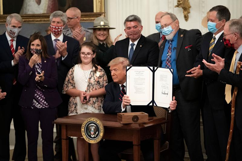President Donald Trump signs the Great American Outdoors Act during a singing ceremony in the East Room of the White House on Aug. 4 in Washington, D.C. (Drew Angerer via Getty Images)