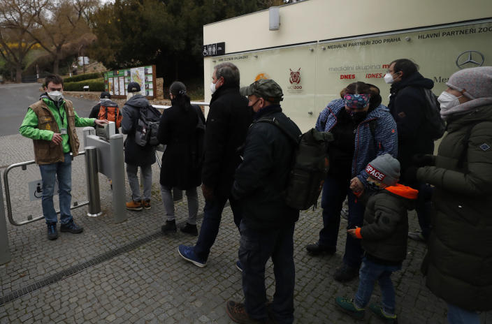 Visitors line up to enter the zoo in Prague, Czech Republic, Monday, April 12, 2021. The Czech government has agreed to start easing the tight lockdown, caused by the COVID-19 pandemic, in one of the hardest-hit European countries. Children up to the fifth grade will be back at schools while the stores selling clothes and shoes for kids, laundries, outdoor farmers markets, zoo and botanical gardens are reopened. (AP Photo/Petr David Josek)