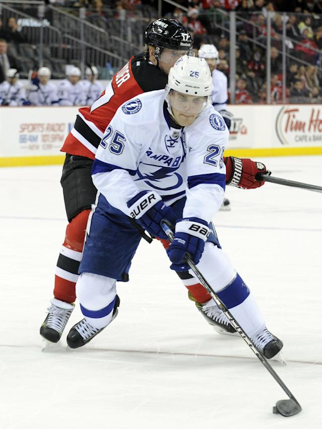 Tampa Bay Lightning defenseman Matthew Carle handles the puck as he gets by New Jersey Devils' Michael Ryder during the first period of an NHL hockey game, Saturday, Dec. 14, 2013, in Newark, N.J. (AP Photo/Bill Kostroun)