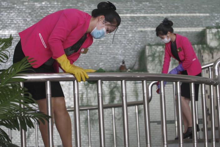 Restaurant staff, wearing face mask, disinfect the handrail of Chongchun Restaurant in Pyongyang, on Thursday, May 13, 2021. (AP Photo/Cha Song Ho)