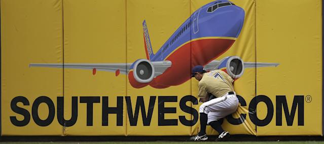 Milwaukee Brewers right fielder Norichika Aoki runs into the wall after catching a long fly ball hit by Los Angeles Angels' J.B. Shuck during the first inning of a baseball game Sunday, Sept. 1, 2013, in Milwaukee. (AP Photo/Morry Gash)