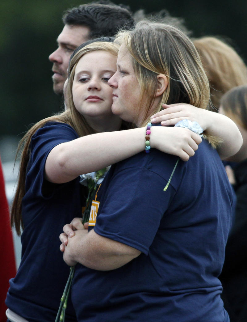 Mourners hug during an interment service  at the Cedar Green Cemetery in Clayton, N.J., on Saturday Oct, 27, 2012, for Autumn Pasquale, a 12-year-old police said was killed by two teenage brothers in their small New Jersey town. Police said the brothers killed the girl and put her body in a recycling bin. (AP Photo/Joseph Kaczmarek)