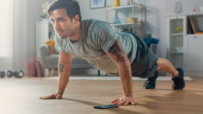 Athletic Fit Man in T-shirt and Shorts is Doing Push Up Exercises While Using a Stopwatch on His Phone. He is Training at Home in His Living Room with Minimalistic Interior.