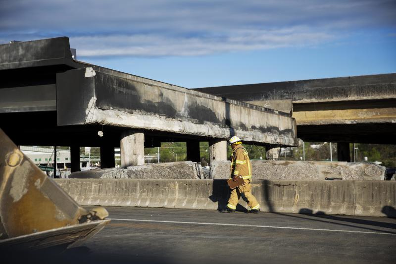 A firefighter walks past a section of an overpass that collapsed from a large fire on Interstate 85 in Atlanta, Friday, March 31, 2017. Many commuters in some of Atlanta's densely populated northern suburbs will have to find alternate routes or ride public transit for the foreseeable future after a massive fire caused a bridge on Interstate 85 to collapse Thursday, completely shutting down the heavily traveled highway. (AP Photo/David Goldman)