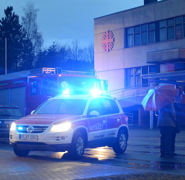 Firefighters stand in front of a workshop for disabled people in Titisee-Neustadt, southwestern Germany, Monday, Nov. 26, 2012 where a fire broke out killing 14 people and injuring at least seven others, authorities said. The center employs some 120 people with either mental or physical disabilities in a variety of jobs including metalwork, woodwork and electrical installation, according to the facility's website. (AP Photo/dapd, Winfried Rothermel)
