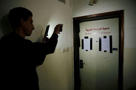 A Palestinian man uses his mobile phone to photograph a door of a Palestinian map office, covered with an Israeli police warrant and taped on the sides by Israeli security officers who carried out an Israeli police order to close the office, in the Arab East Jerusalem neighbourhood of Beit Hanina March 14, 2017. REUTERS/Ammar Awad