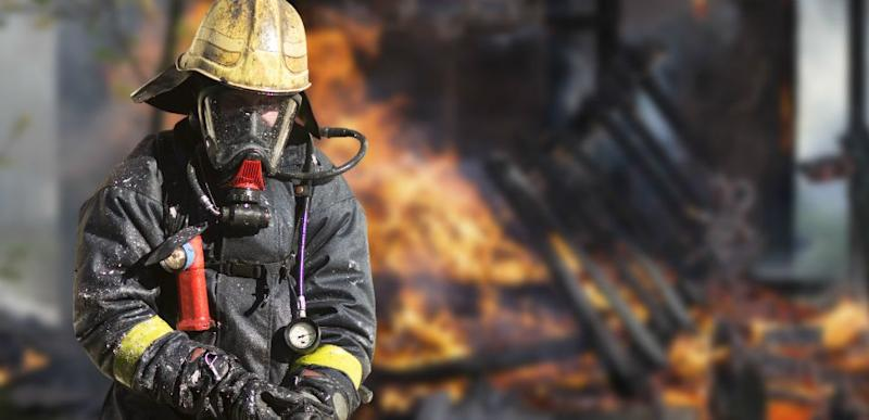 Fire fighter with protective gear stands outside a house blaze