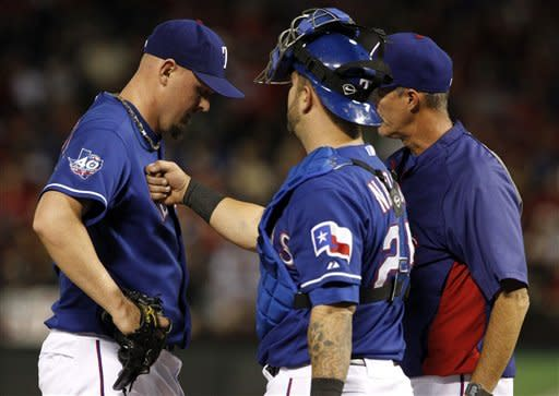 Texas Rangers starting pitcher Matt Harrison, left, takes a tap to the chest from catcher Mike Napoli as pitching coach Mike Maddux, right, visits the mound in the fifth inning of a baseball game against the Tampa Bay Rays, Friday, April 27, 2012, in Arlington, Texas. (AP Photo/Tony Gutierrez)