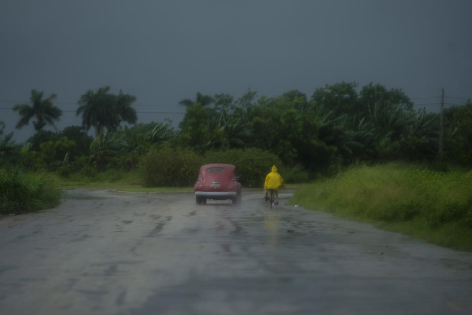 A man rides a bicycle alongside a car in rain caused by Hurricane Ida, in Guanimar, Artemisa province, Cuba, Saturday Aug. 28, 2021. (AP Photo/Ramon Espinosa)