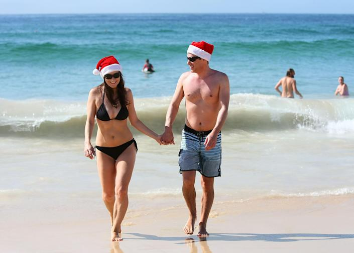 SYDNEY, AUSTRALIA - DECEMBER 25: Vivian Vasso and Ben Cheathan stroll hand in hand from the water at Bondi Beach on December 25, 2011 in Sydney, Australia. Bondi Beach is a popular place for tourists on Christmas Day. (Photo by Don Arnold/Getty Images)