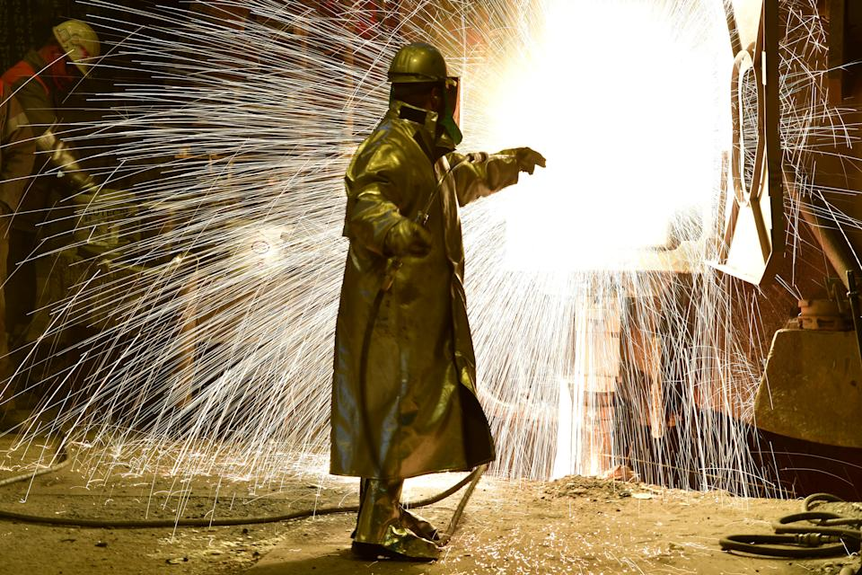 An employee works in front of the blast furnace past rolls of sheet steel at a mill of German steel producer Salzgitter AG on March 1, 2018 in Salzgitter, Germany. Photo: Alexander Koerner/Getty Images