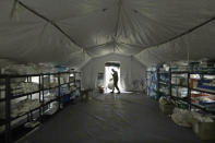 A U.S. Army soldier walks inside a mobile surgical unit being set up by soldiers from Fort Carson, Col., and Joint Base Lewis-McChord (JBLM) as part of a field hospital inside CenturyLink Field Event Center, Tuesday, March 31, 2020, in Seattle. Soldiers from the 627th Army Hospital at Fort Carson, will join soldiers from JBLM to staff the 250-bed hospital to be used for non-COVID-19 cases, allowing local hospitals additional space for patients affected by the coronavirus outbreak. Officials said that the field hospital is expected to be ready to receive patients next week. (AP Photo/Elaine Thompson)