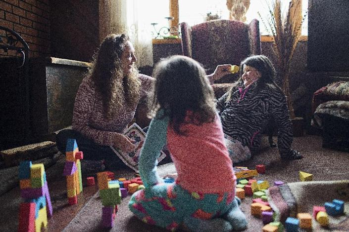 In this Monday, Dec. 19, 2016, photo, Donna Dye, who is unemployed and whose husband is disabled, plays with her two granddaughters, Lilly, left, and Chloe, at her home where she cares for them, in Minnie, Ky. Dye and her husband have been fighting the federal government to keep his Social Security disability checks after a local lawyer who helped them became the subject of a federal fraud investigation. (AP Photo/David Stephenson)