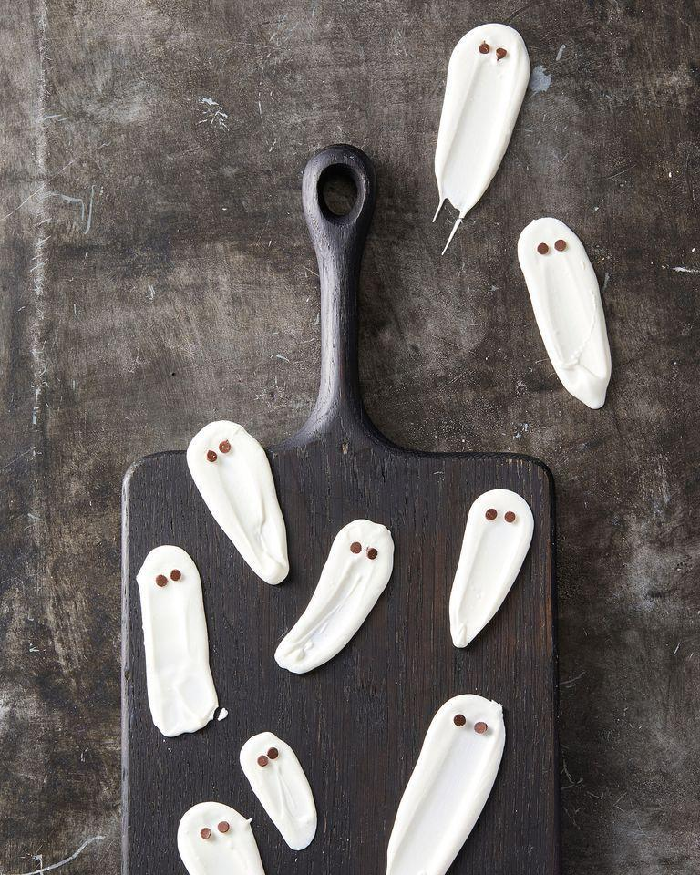 """<p>Tiny chocolate chips turn smears of melted white chocolate into ghosts.</p><p><em><strong>Get the recipe at</strong></em> <em><strong><a href=""""https://www.goodhousekeeping.com/food-recipes/party-ideas/a28591376/white-chocolate-ghosts-recipe/"""" rel=""""nofollow noopener"""" target=""""_blank"""" data-ylk=""""slk:Good Housekeeping"""" class=""""link rapid-noclick-resp"""">Good Housekeeping</a>.</strong></em></p>"""