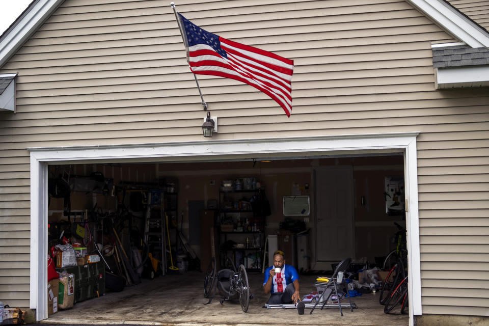 Freddie De Los Santos sits in his garage before his daily training in Hopewell Junction, N.Y., on Wednesday, Aug. 19, 2021. De Los Santos, 51, who grew up in a rough New York City neighborhood at the height of the crack cocaine epidemic, has created an idyllic small-town life north of the city. (AP Photo/Emilio Morenatti)