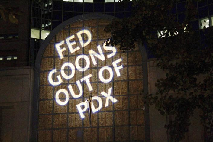"""Protesters projected the words """"Fed goons out of PDX"""" on the front of the Multnomah County Justice Center"""