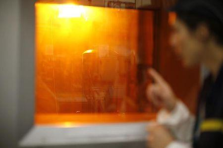 A worker looks through a thick glass window at part of the treatment of nuclear waste at the Areva Nuclear Plant of La Hague, near Cherbourg, western France, western France