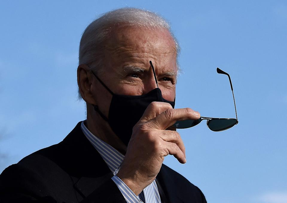 President Joe Biden takes off his sunglasses as he walks across the White House South Lawn upon his return from Camp David.