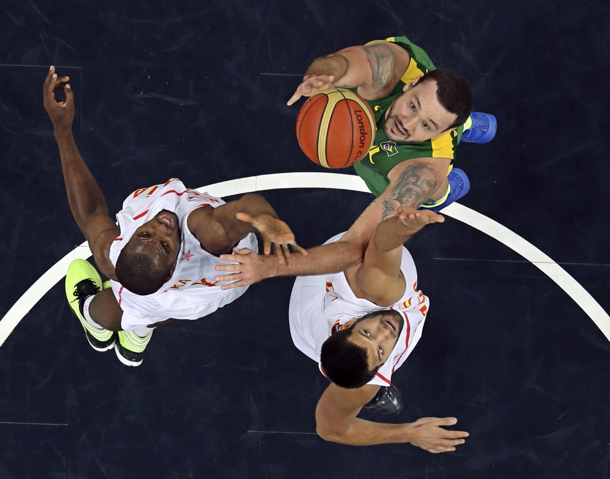 Brazil's Caio Torres (R) and Spain's Felipe Reyes and Serge Ibaka (L) reach for the rebound during their men's preliminary round Group B basketball match at the Basketball Arena during the London 2012 Olympic Games August 6, 2012.                        REUTERS/Sergio Perez (BRITAIN  - Tags: OLYMPICS SPORT BASKETBALL)