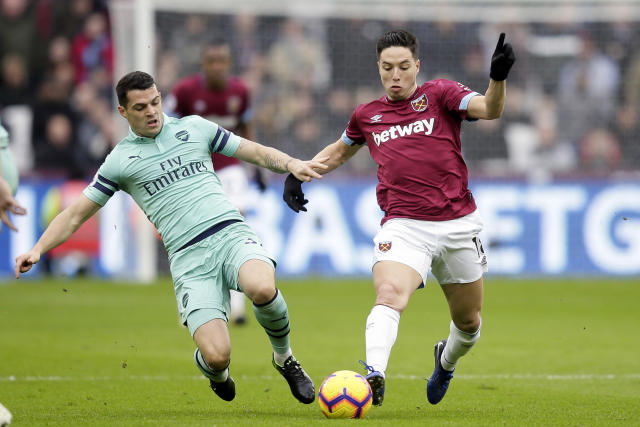 Arsenal's Granit Xhaka tackles West Ham's Samir Nasri, right, during the English Premier League soccer match between West Ham United and Arsenal at London Stadium in London, Saturday, Jan. 12, 2019. (AP Photo/Tim Ireland)