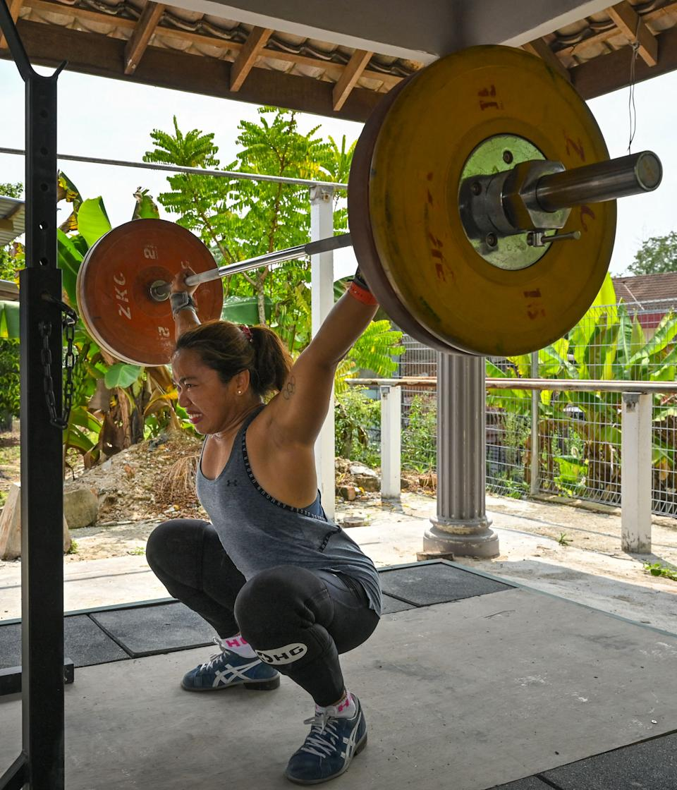 This picture taken on May 21, 2021 shows Olympic weightlifter Hidilyn Diaz of the Philippines lifting weights during a training session in Jasin in the Malaysian city of Malacca. - Filipina weightlifter Hidilyn Diaz, who took silver at Rio 2016, has been stuck in Malaysia since February last year because of the coronavirus pandemic but has remained determined to realise her dream of becoming the first Olympic gold medal winner from the Philippines. - To go with 'OLY-2020-2021-WEIGHTLIFTING-PHILIPPINES,INTERVIEW' (Photo by Mohd RASFAN / AFP) / To go with 'OLY-2020-2021-WEIGHTLIFTING-PHILIPPINES,INTERVIEW' (Photo by MOHD RASFAN/AFP via Getty Images)
