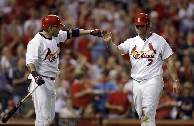 St. Louis Cardinals' Matt Holliday, right, is congratulated by teammate Yadier Molina after scoring on a double by Allen Craig during the sventh inning of a baseball game against the Arizona Diamondbacks on Thursday, May 22, 2014, in St. Louis. (AP Photo/Jeff Roberson)
