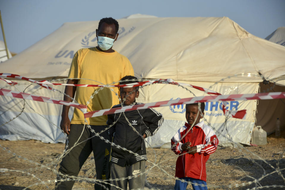 Migrants stand inside the new temporary refugee camp in Kara Tepe, on the northeastern island of Lesbos, Greece, Saturday, Sept. 19, 2020. Police on the Greek island of Lesbos on Friday resumed relocating migrants rendered homeless when fires ravaged the country's largest refugee camp amid a local COVID-19 outbreak. (AP Photo/Panagiotis Balaskas)