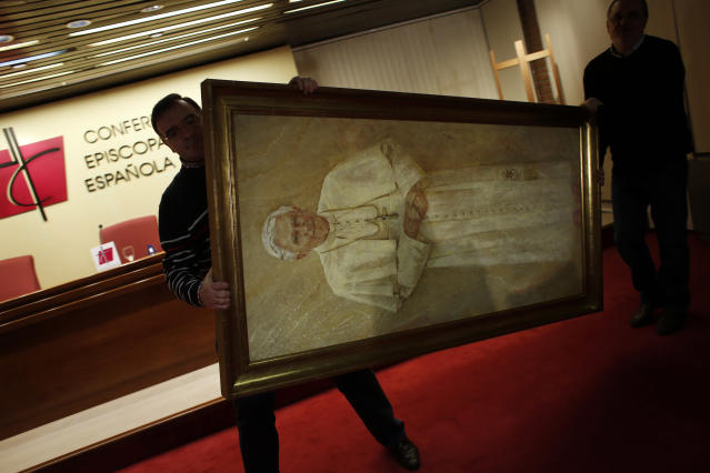 "Workers remove a painting of Pope Benedict XVI from the press conference room after the head of Spain's Catholic Church and President of the Bishops' Conference Cardinal Antonio Maria Rouco Varela addressed a news conference in Madrid February 11, 2013. Pope Benedict shocked the world on Monday by saying he no longer had the mental and physical strength to cope with his ministry, in an announcement that left his aides ""incredulous"" and will make him the first pontiff to step down since the Middle Ages. REUTERS/Susana Vera (SPAIN - Tags: RELIGION POLITICS TPX IMAGES OF THE DAY) - RTR3DNAY"
