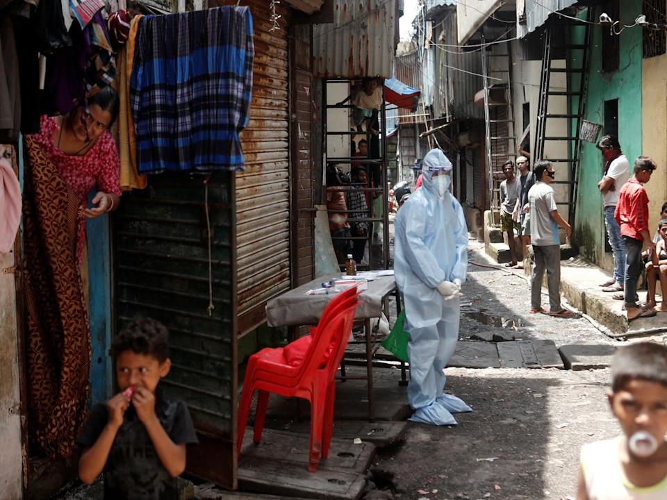 A healthcare worker waits to test residents during a medical campaign for the coronavirus disease (COVID-19) at a slum area in Mumbai, India, on June 30, 2020.
